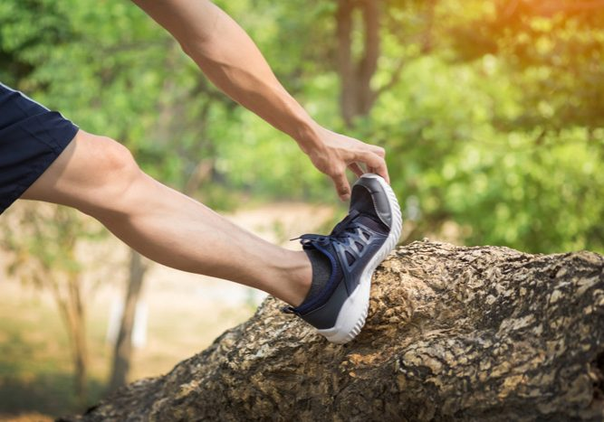 man stretching leg as warm-up before run.